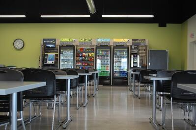 An employee break room or enrichment area with vending machines and tables to sit at, designed by A.C.E. Building service