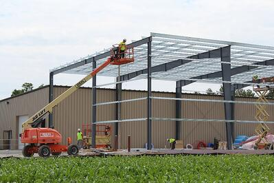 An expansion construction project in progress for a manufacturing facility building using metal building systems